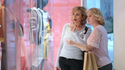 Excited women looking at clothes in store window