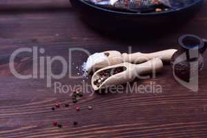 Mixture of black and red pepper in a wooden spoon