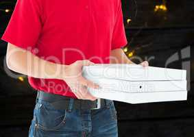 Deliveryman with pizza boxes in foreground. Wood and lights background