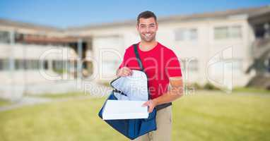 Delivery man removing pizza box from bag against house