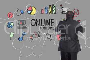 Digital composite image of businessman against various icons and graphs on gray background