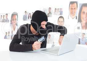 Criminal in hood on laptop with card in front of peoples profile faces