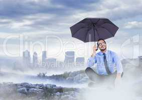 Business man legs crossed with umbrella on misty mountain peak against skyline
