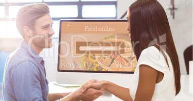 Man and woman shaking hands with search screen on monitor