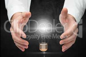 Digitally generated image of hand covering electric bulb against gray background