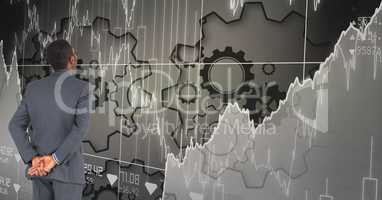 Digital composite image of businessman looking at graphs and gears on grid