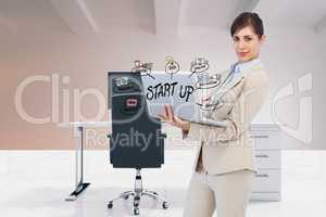 Digital composite image of businesswoman using laptop with start up text and icons in office