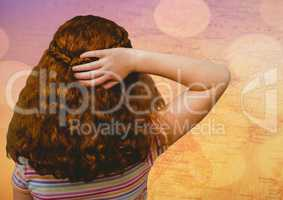 Back of girl with hand on hair against map with bokeh