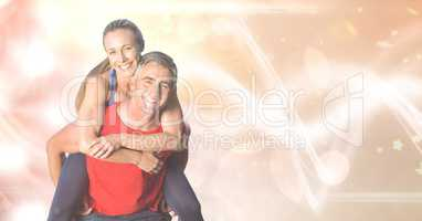 Happy fit man giving piggyback ride to woman over bokeh