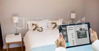 Hands using smart home app on tablet PC in bedroom