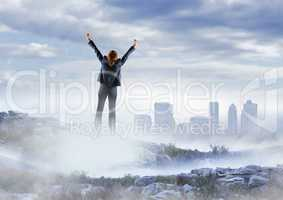 Business woman cheering on misty mountain peak against skyline