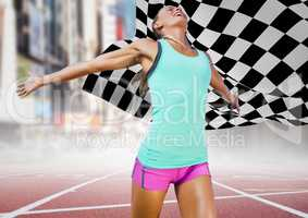 Female runner on track against blurry street and checkered flag