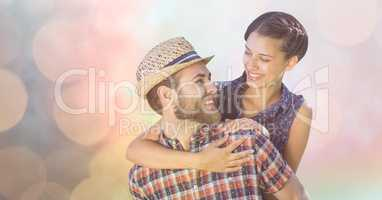 Happy man giving piggyback ride to woman over bokeh