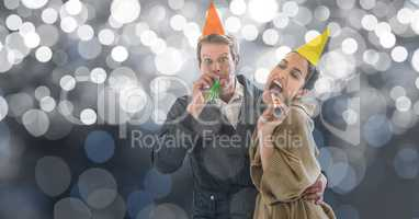 Happy couple blowing party horns against blur background