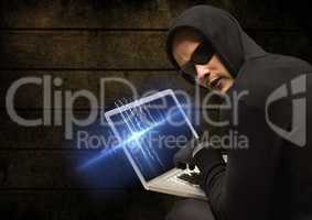 Criminal in hood on laptop in front of wood