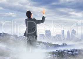 Business man hands up on misty mountain peak against skyline