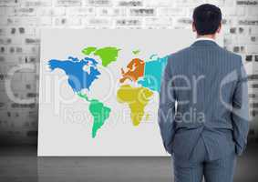 Businessman looking at Colorful Map with brick wall background