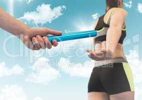 Relay runner and hand with blue baton against sky with flares