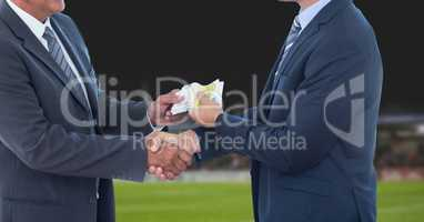 Midsection of businessmen passing money representing corruption concept