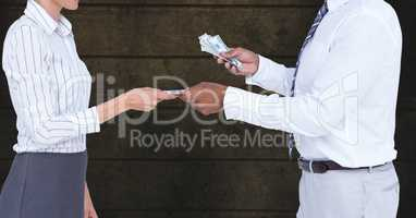 Midsection of businessman giving money to colleague representing corruption concept