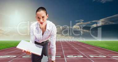 Digital composite image of businesswoman with laptop at starting point on racing track