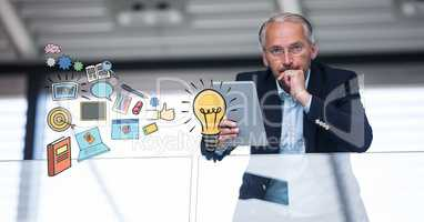 Businessman holding tablet PC with idea icons in foreground