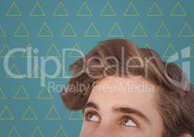 Top of man's head against blue background with yellow triangle pattern
