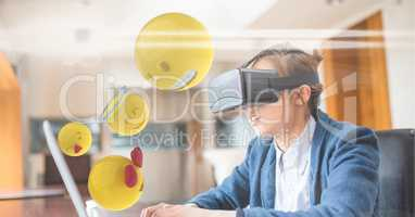 Digitally generated image of emojis flying by businessman wearing VR glasses while using laptop at d