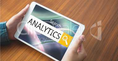 Hands holding tablet PC with analytics text in search box