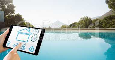 Hands using smart home app on tablet PC by pool