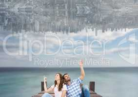 up side down city in the sky over the sea with couple sit on a dock and looking up