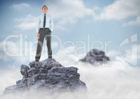 Business man hand in pocket on mountain peak in clouds