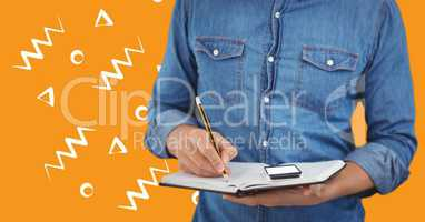 Man denim shirt mid section with notebook against orange background with white patterns