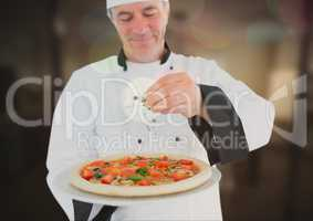 Chef pouring oregano to the pizza in the restaurant