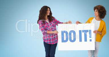 Female friends holding billboard with do it text against blue background