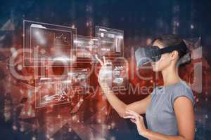 Digital composite image of woman touching futuristic screen while using VR glasses