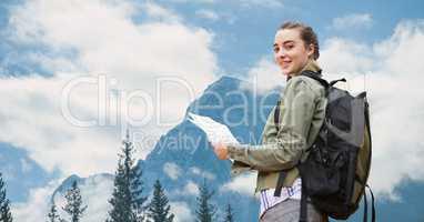 Female traveler holding maps against mountain