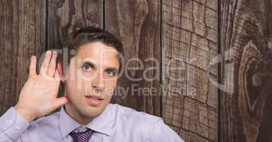 Businessman with hand on ear listening over wooden wall