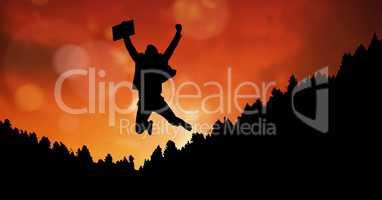 Silhouette businessman in midair against orange sky