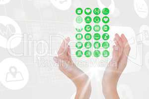 Digital composite image of hand covering various icons against tech graphics
