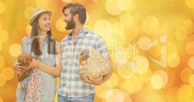 Happy couple with eggs and hen over bokeh