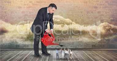 Digital composite image of businessman pouring water on employees from watering can