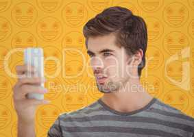 Man with phone against yellow emoji pattern