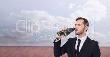 Shocked businessman looking away while holding binoculars