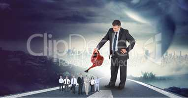 Digital composite image of businessman watering employees on highway with cityscape in background
