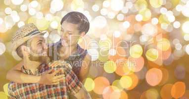 Happy man giving piggyback rise to woman over blur background