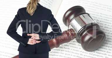 Midsection rear view of businesswoman with fingers crossed standing in front of gavel and law book