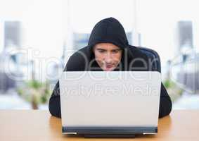 Criminal in hood on laptop by windows