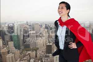 Happy businesswoman in super hero costume standing over city