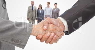 Cropped image of businessmen doing handshake with employees in background